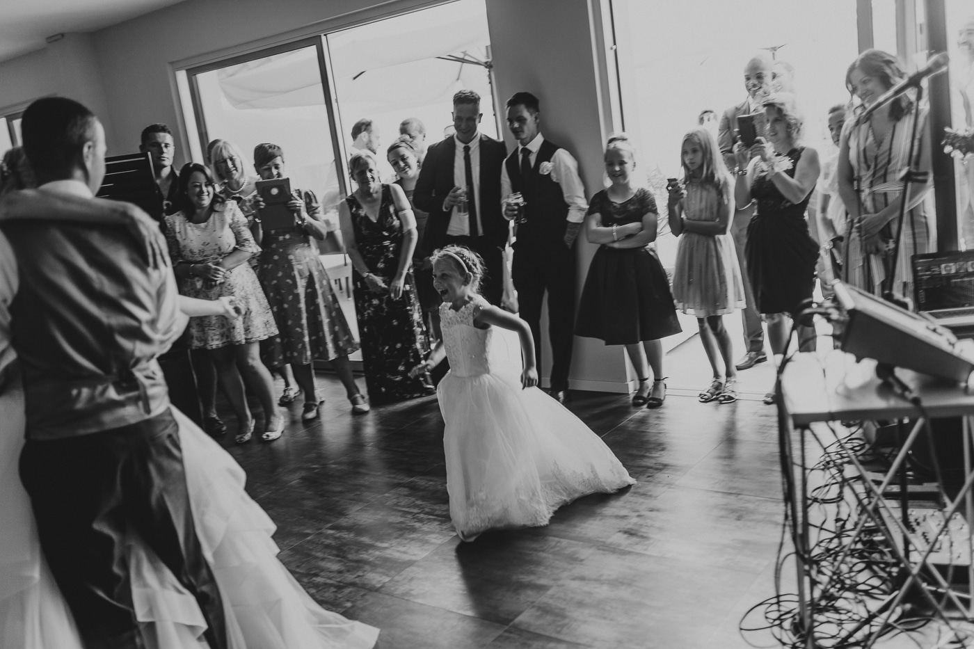 Happy bridesmaid running to meet bride and groom on dance floor with wedding guests surrounding by Joshua Wyborn