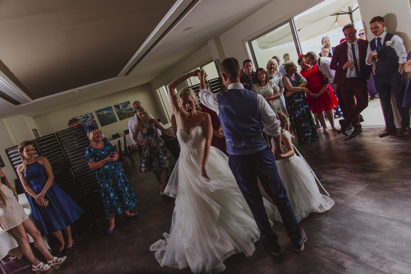 Happy bride spinning on the dance floor by her husband and small bridesmaid whilst wedding guests look on by Joshua Wyborn