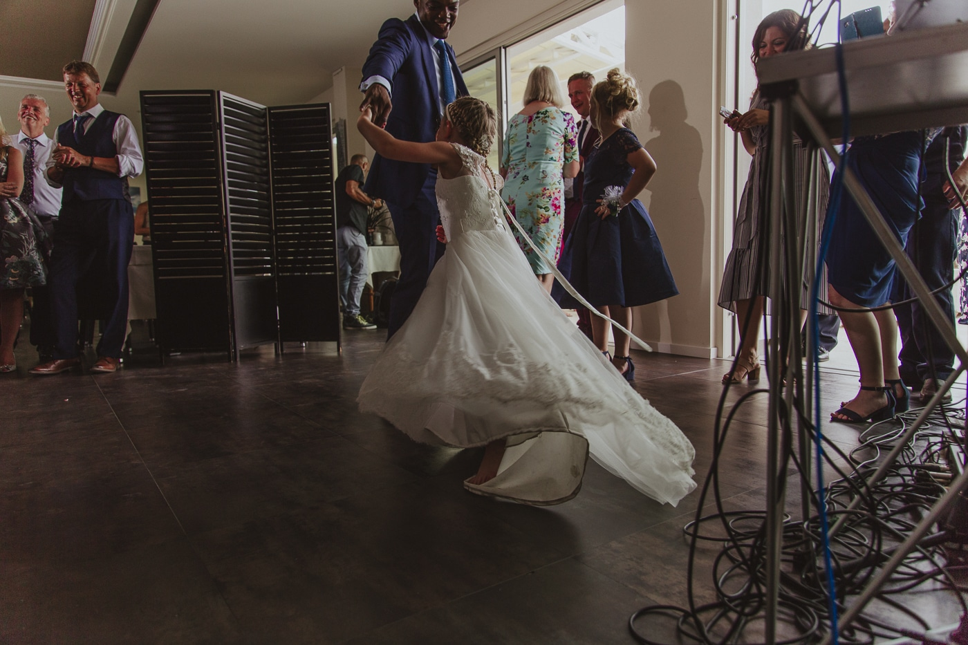 Young bridesmaid dancing letting her white dress spin on the wooden floor amongst the wedding guests by Joshua Wyborn