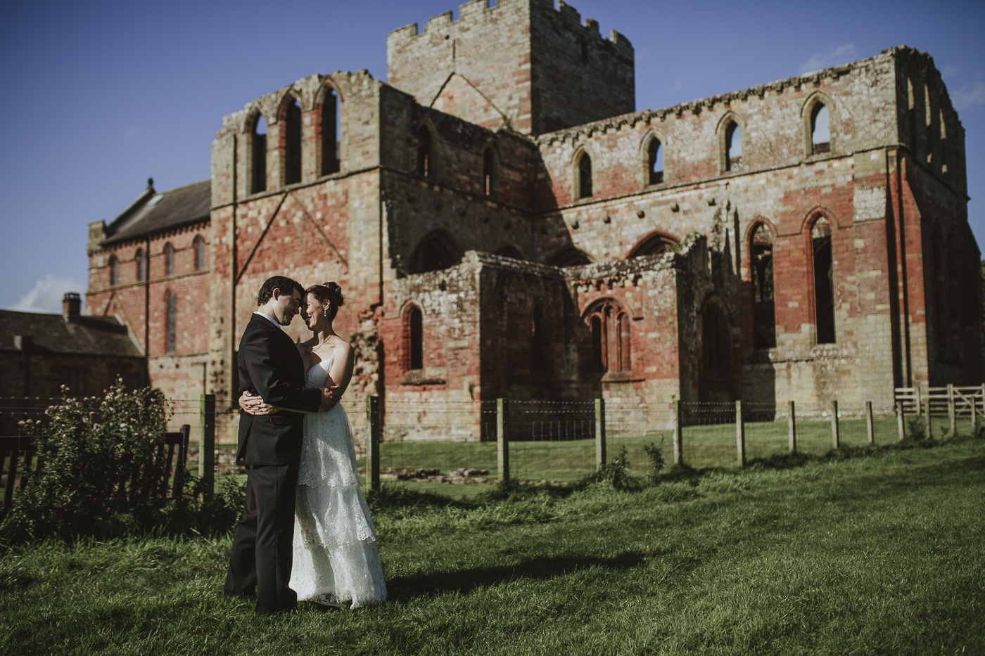 Bride and groom embrace in front of ruins after elopement by Joshua Wyborn Photographic
