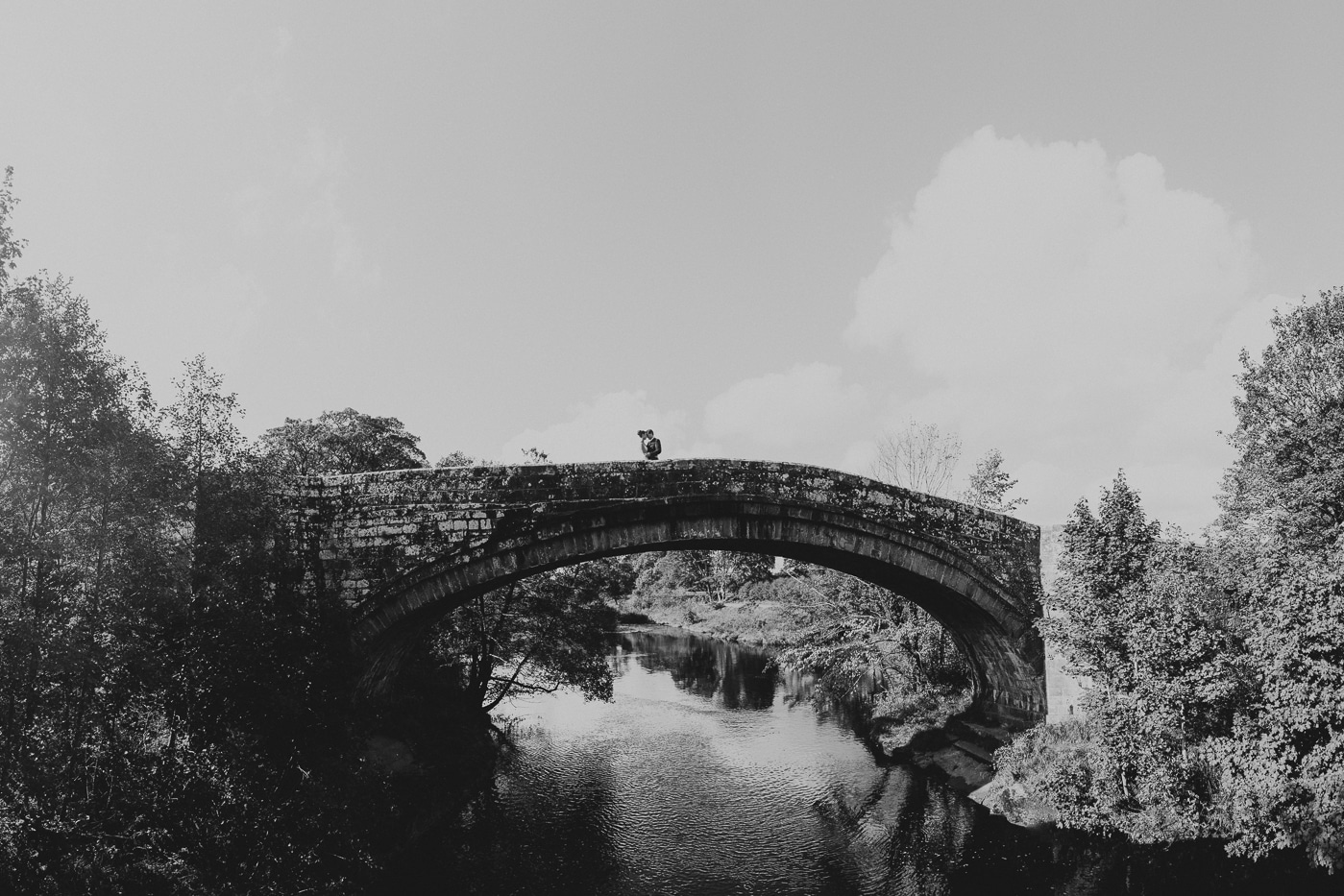 Couple on stone bridge over river after eloping by Joshua Wyborn Photographic