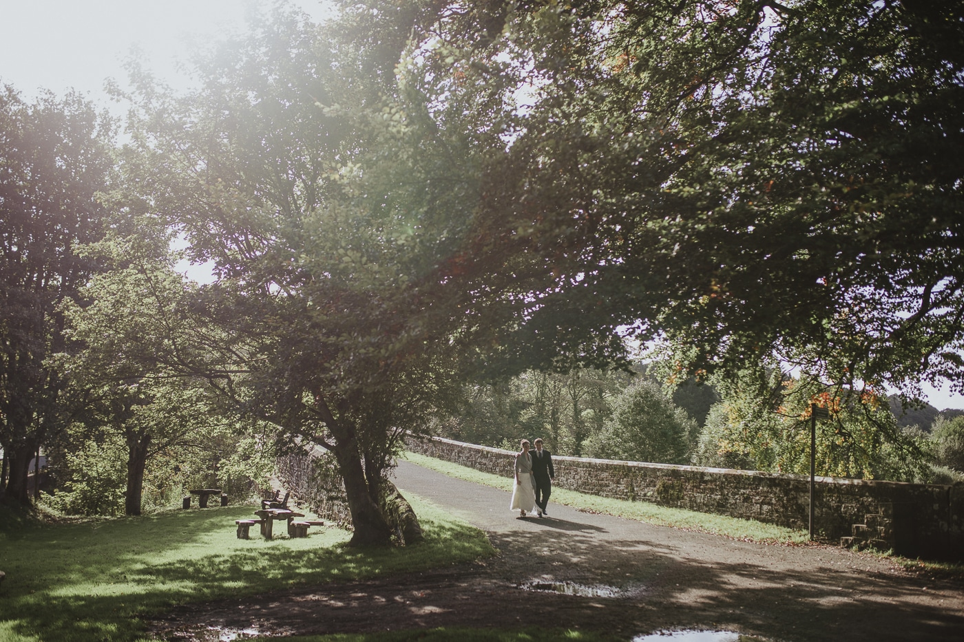 Bride and groom walking under the trees in the sunshine by Joshua Wyborn Photographic