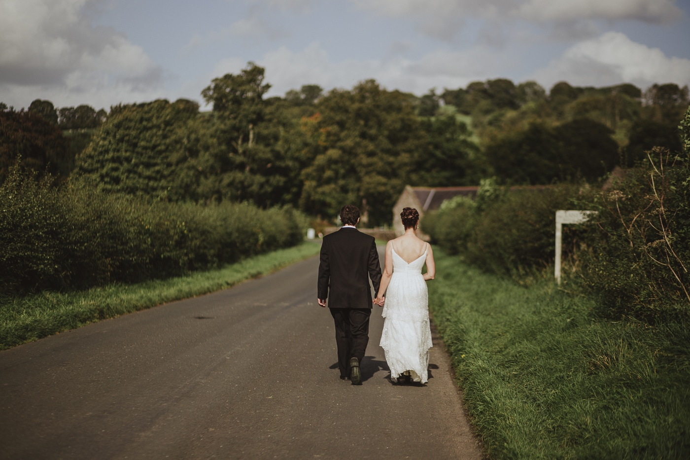 Bride and groom walking down a hedge lined road after eloping by Joshua Wyborn Photographic