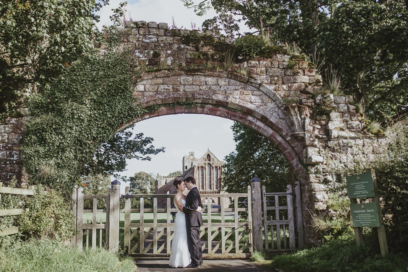 Couple under an archway after eloping by Joshua Wyborn Photographic