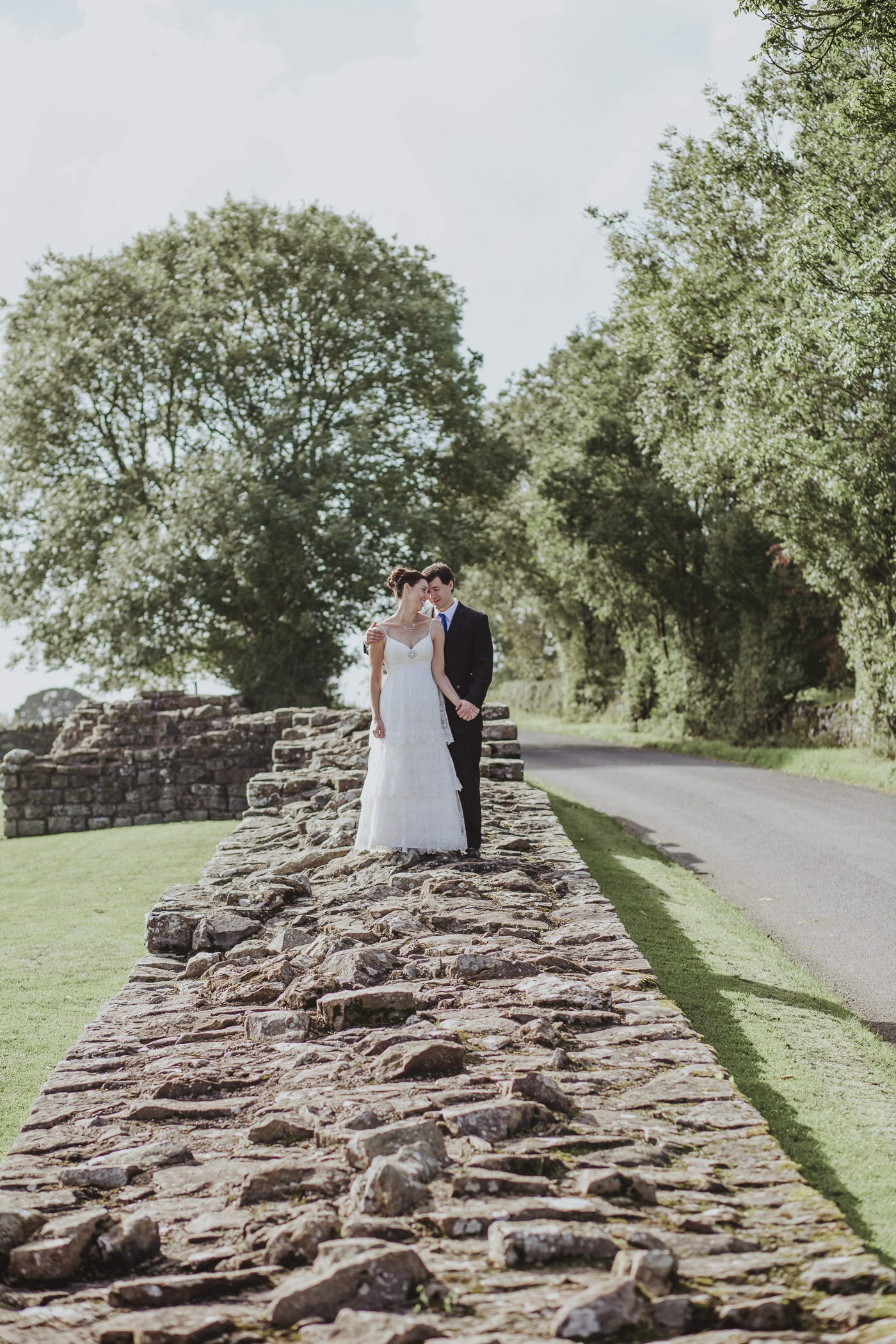 Couple standing together on Hadrians Wall on their elopement from America by Joshua Wyborn