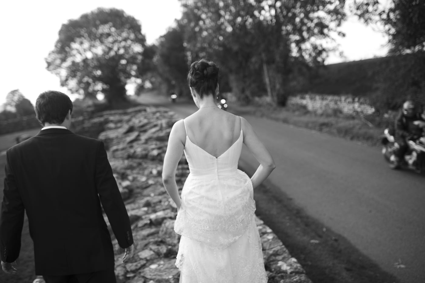 Bride and groom picking their way along a stone wall in dress and suit at Hadrians wall with Joshua Wyborn Photographic