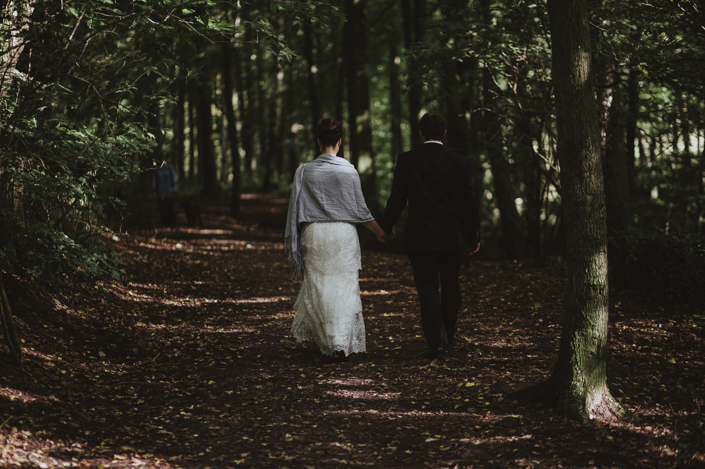 Bride in shawl walking with groom through a woodland path by Joshua Wyborn Photographic