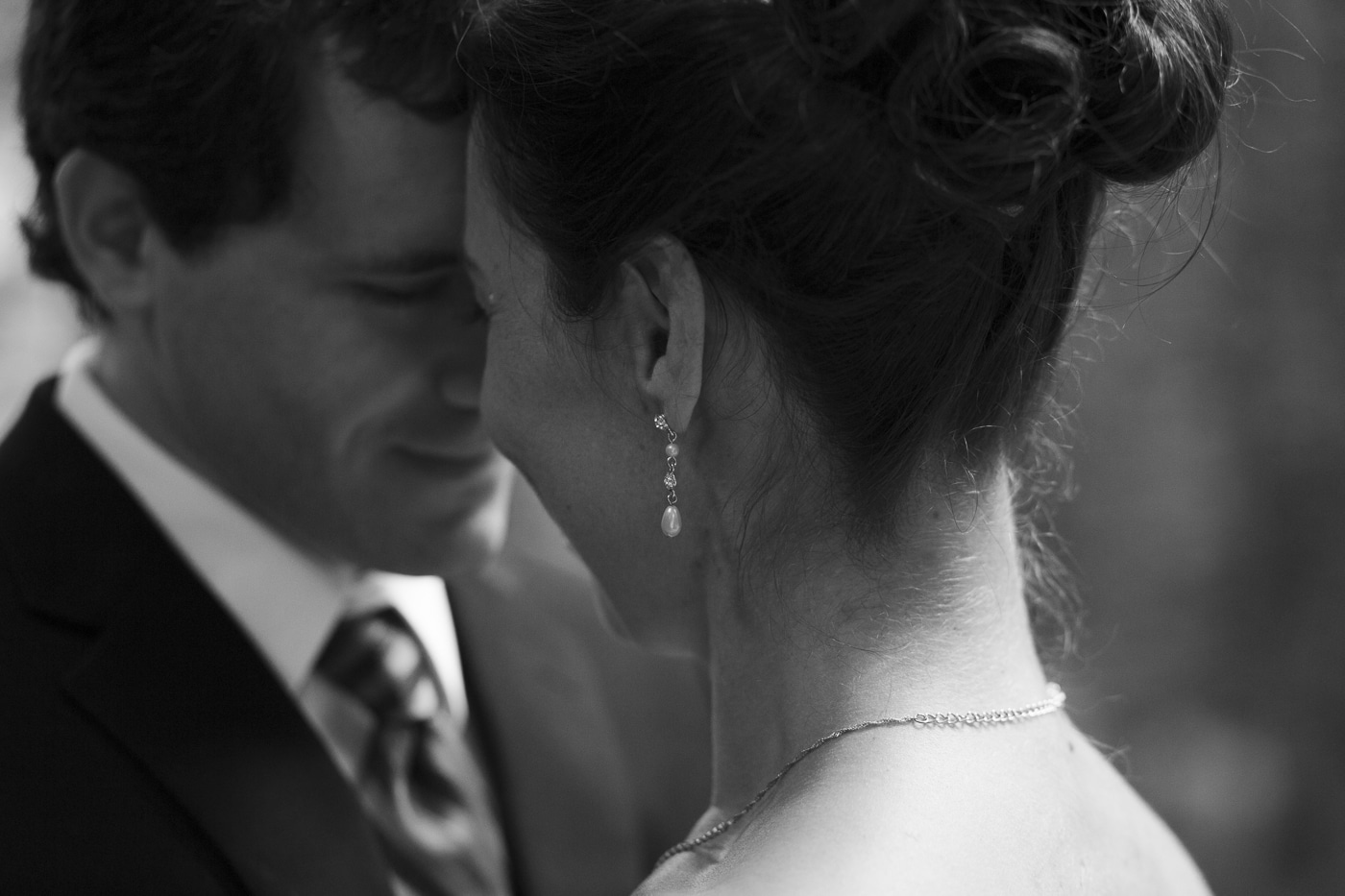 Closeup of bridal hair and jewellery with groom is background by Joshua Wyborn Photographic