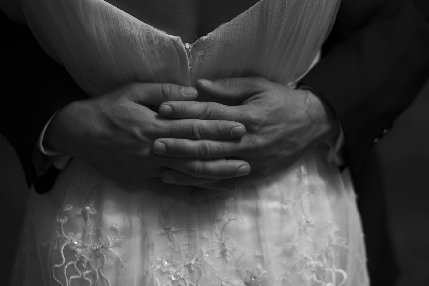 Groom embracing bride with detailed wedding dress by Joshua Wyborn Photographic