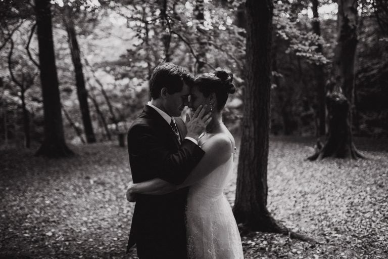 Bride and groom embrace in forest by Joshua Wyborn Photographic