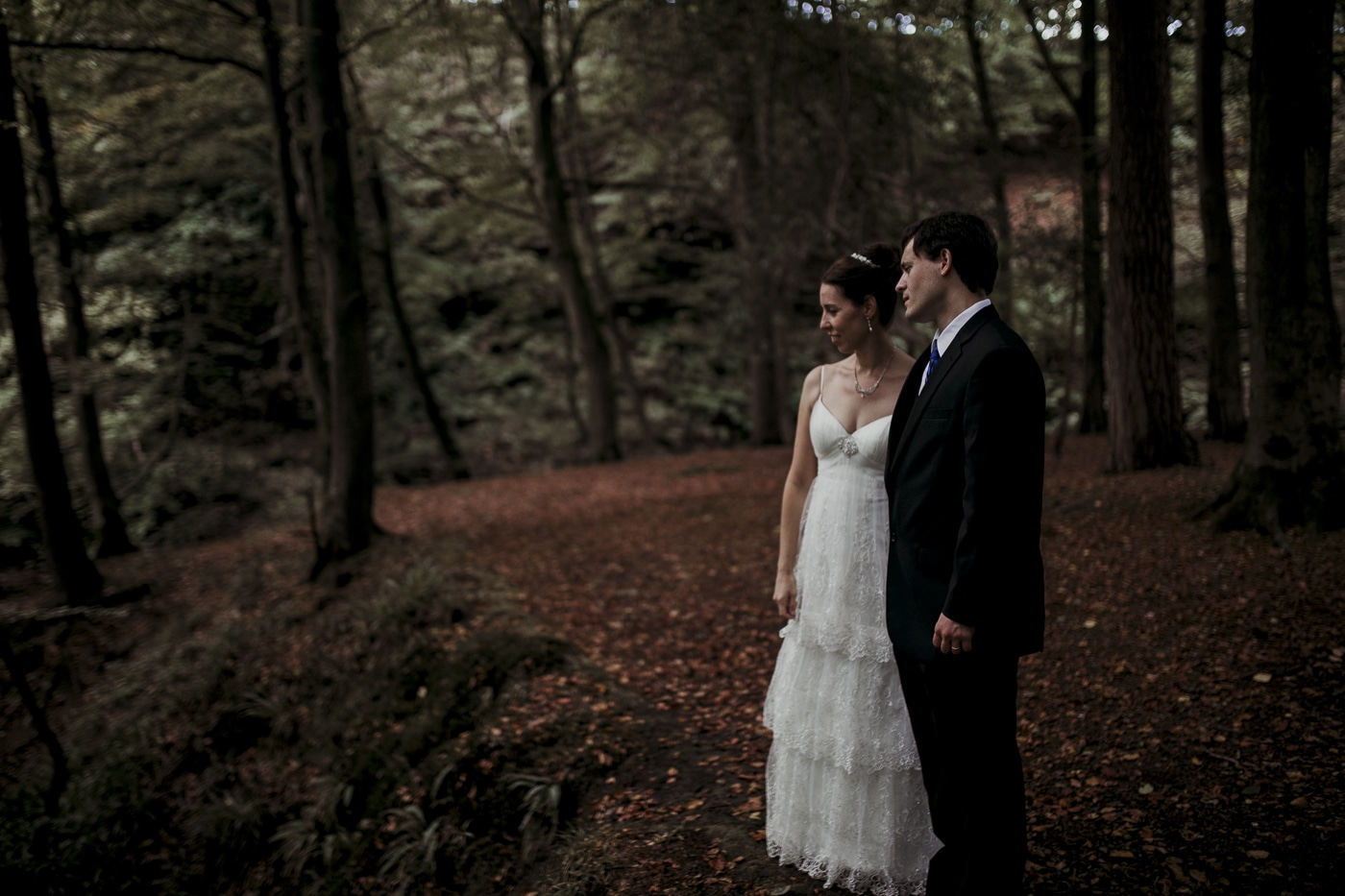 Bride and groom stand in woodland by Joshua Wyborn