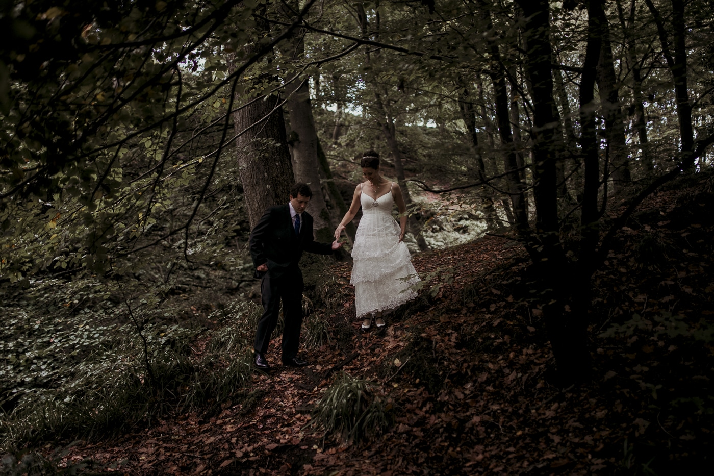 Helping bride through woodland for wedding by Joshua Wyborn photographic