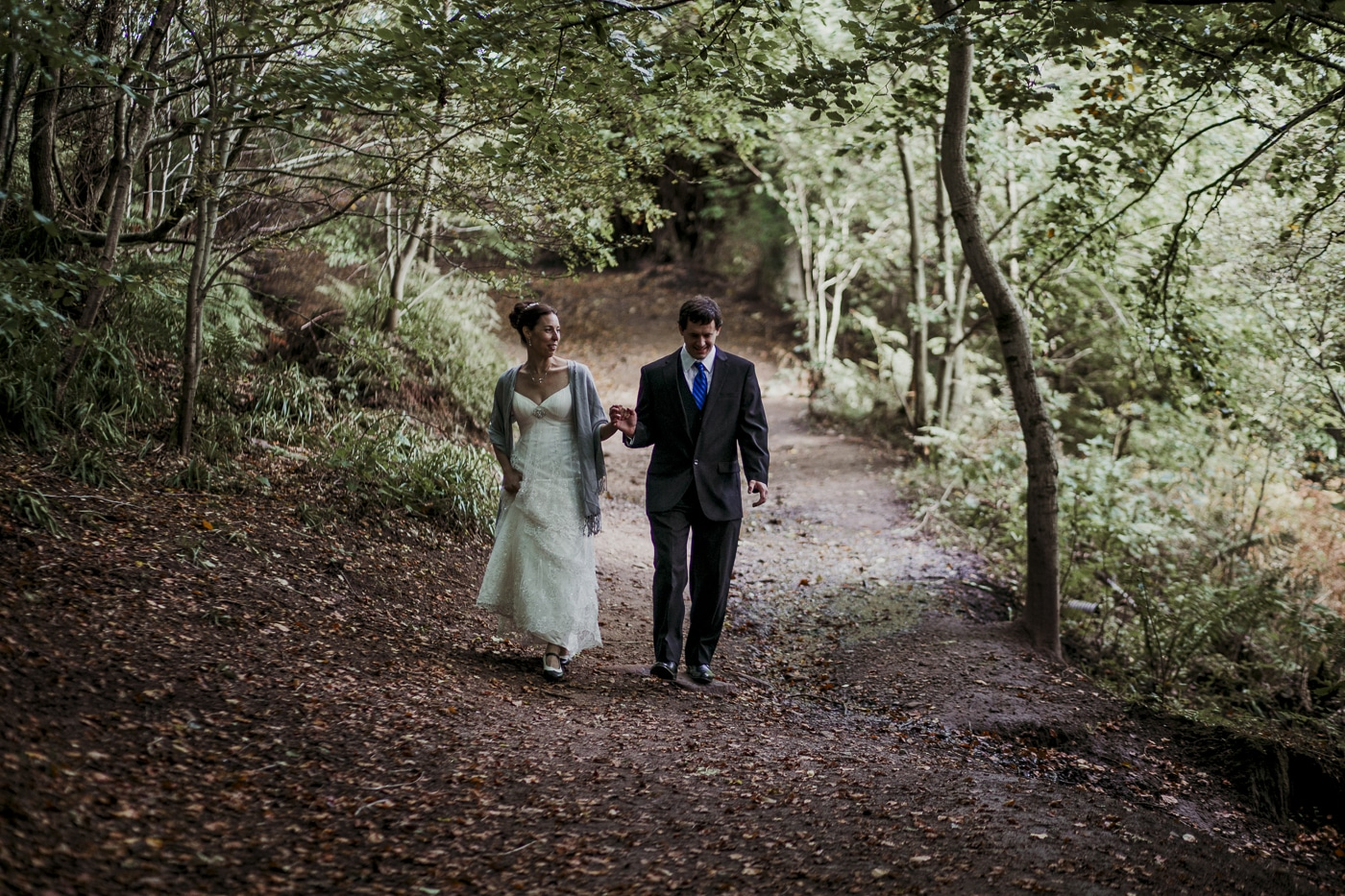 Holding hands through the forest for wedding by Joshua Wyborn photographic