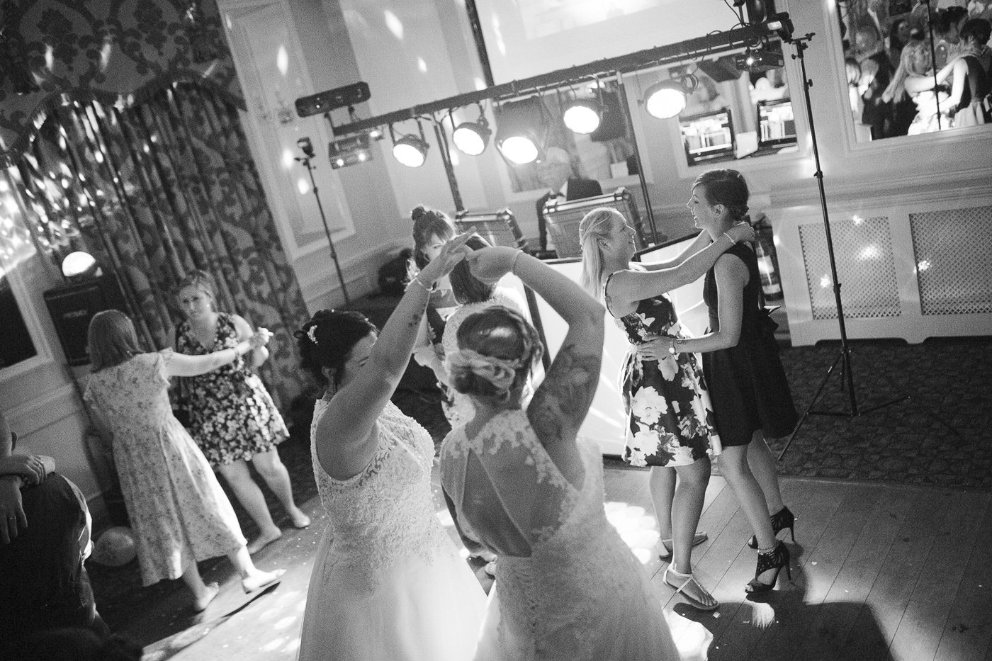 Brides and guests dancing together on the dancefloor for wedding photography by Joshua Wyborn