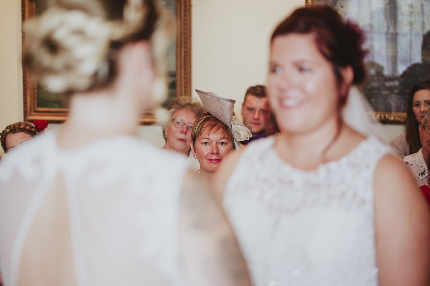 Mother in background of two brides for wedding by Joshua Wyborn photography