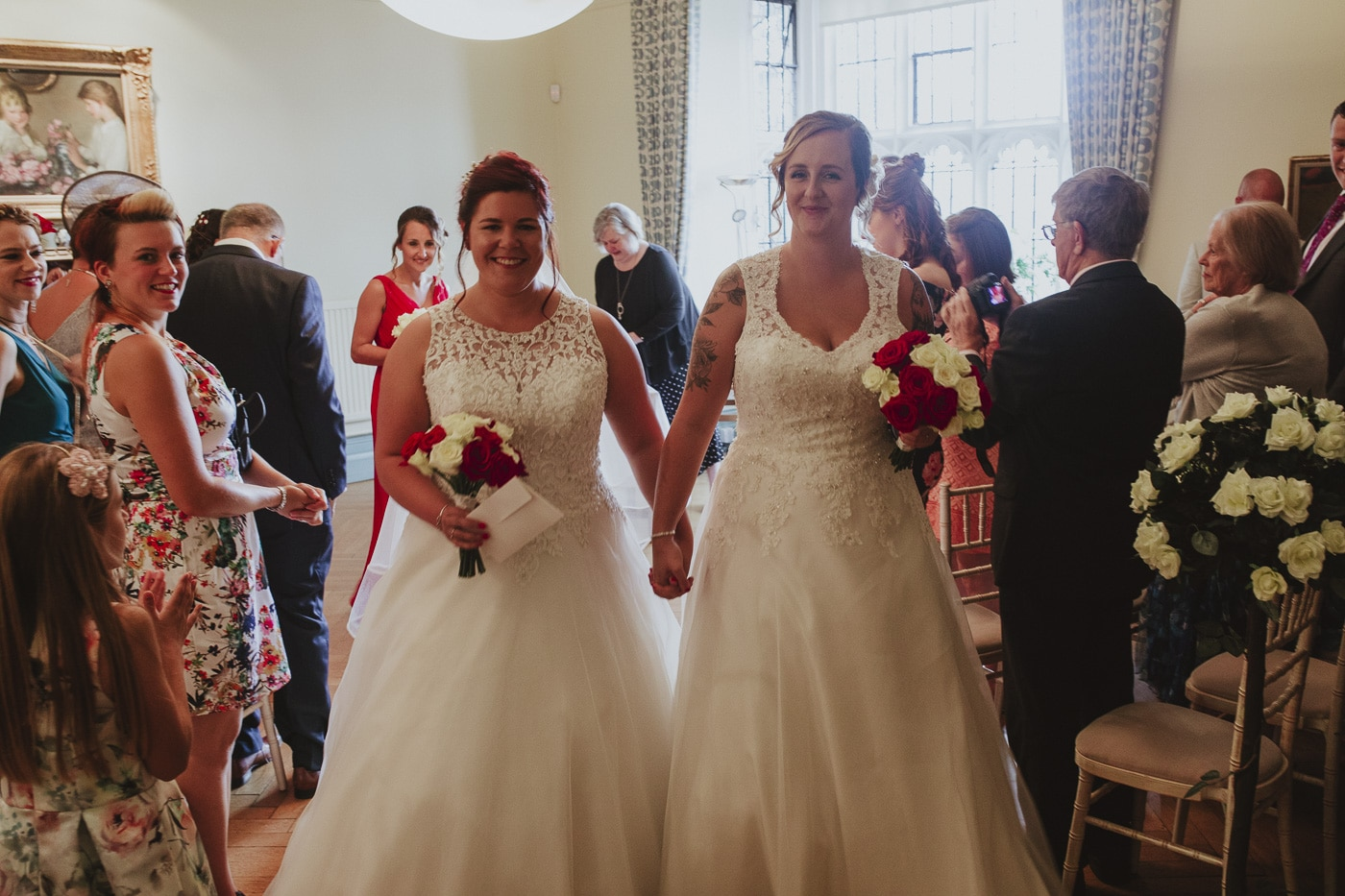 Brides walking down the aisle together for wedding by Joshua Wyborn photography