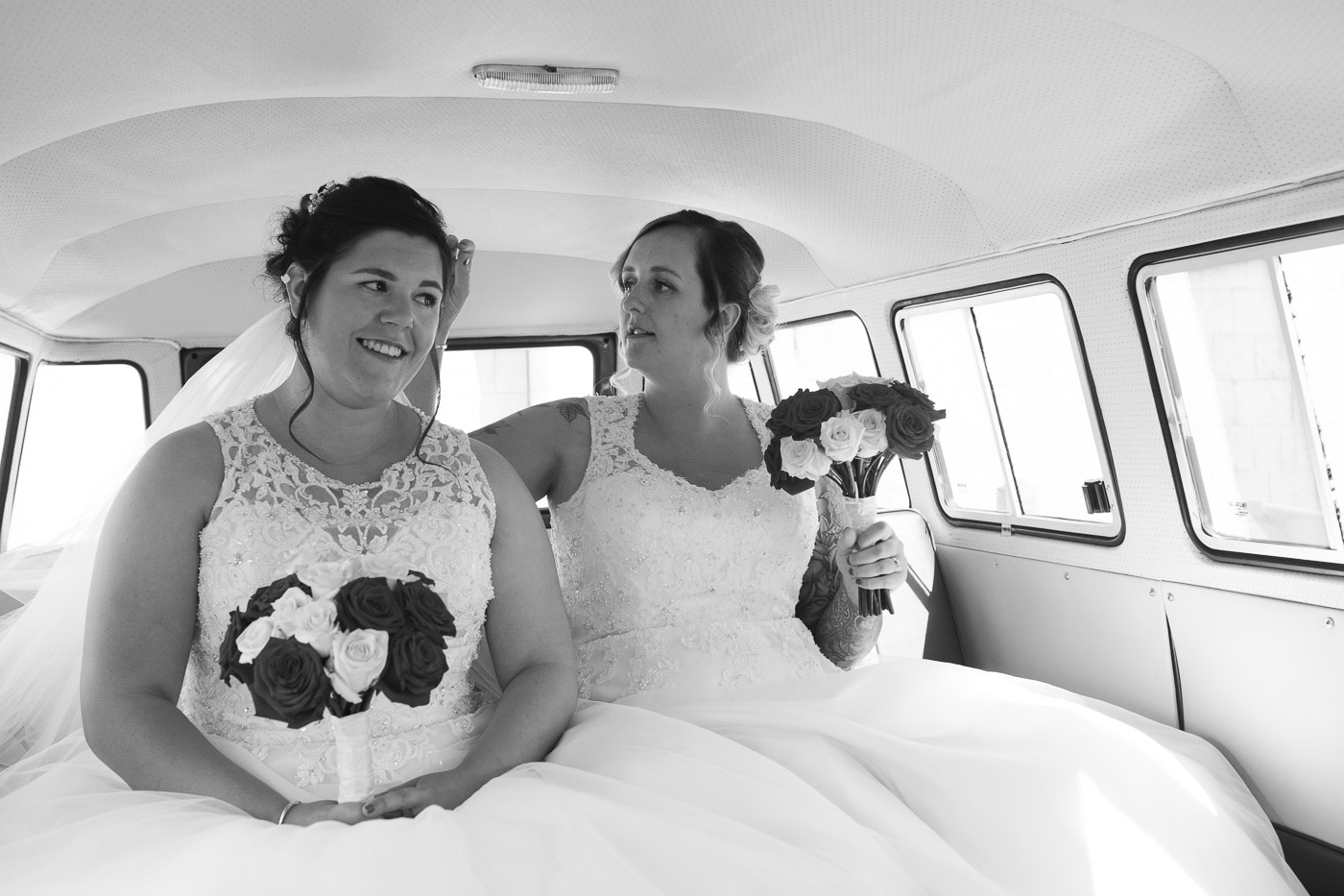 Brides in car together fixing hair for wedding by Joshua Wyborn photography