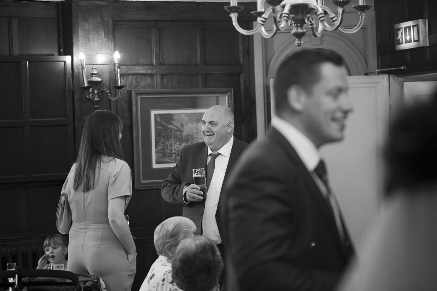 Wedding guests chatting in drinks reception for wedding by Joshua Wyborn photography