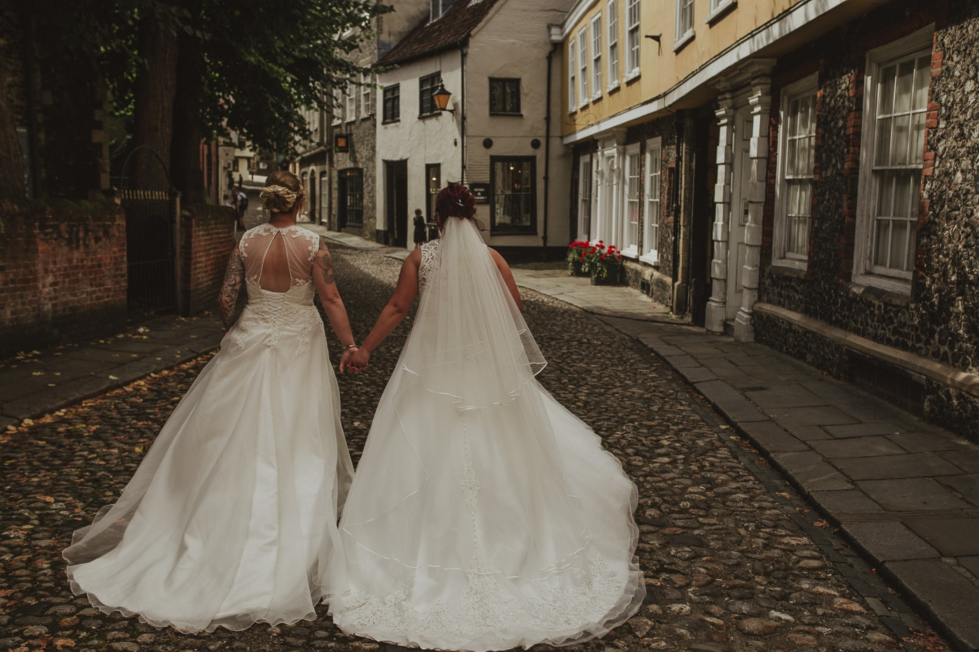 Back of brides walking across cobbles for wedding by Joshua Wyborn photography