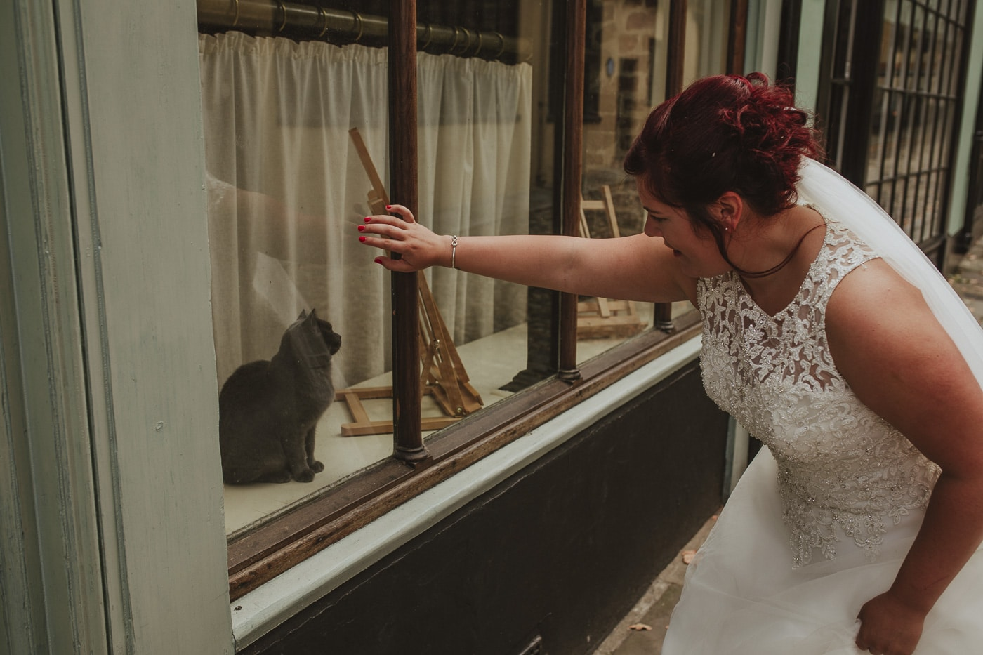 Bride looking at cat through window for wedding by Joshua Wyborn photography