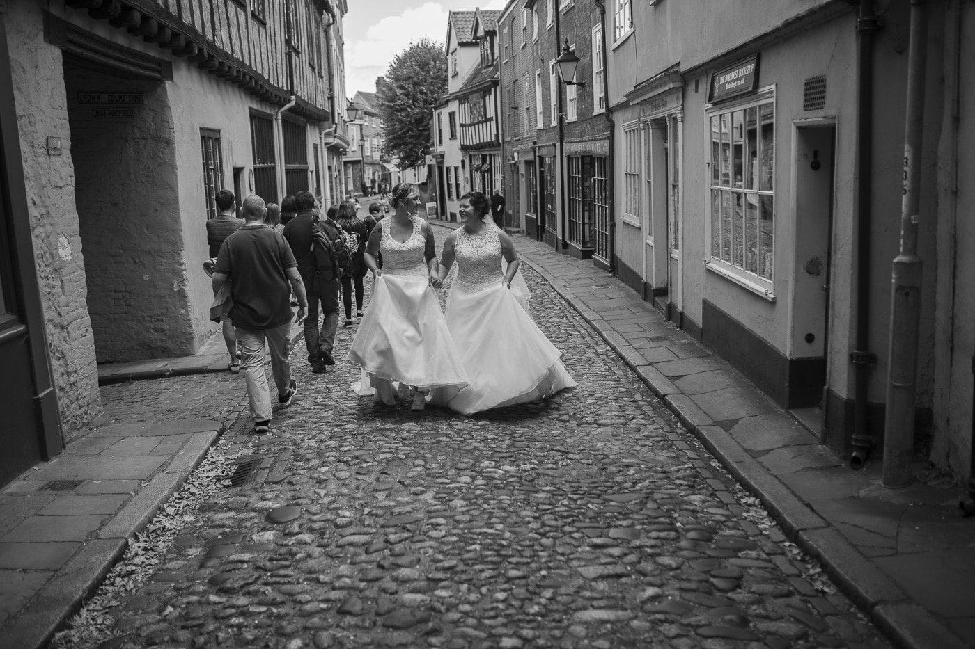 Brides walking on cobbles for wedding by Joshua Wyborn photography