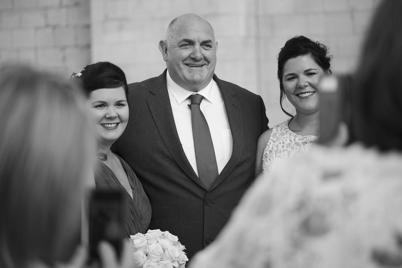 Bride and bridesmaid take photo with dad for wedding by Joshua Wyborn