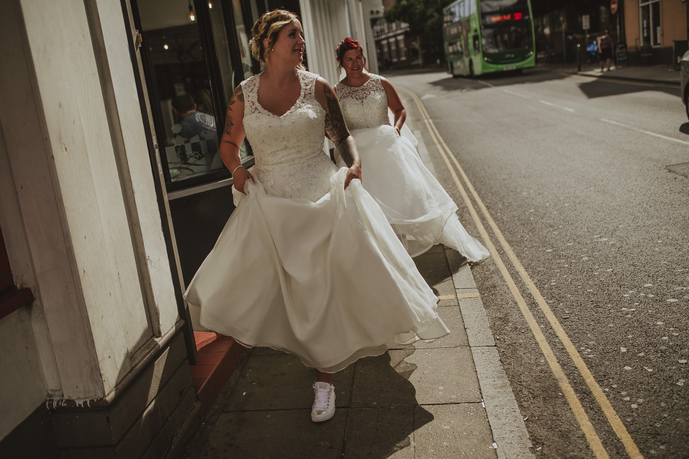 Bride showing trainers under dress for wedding by Joshua Wyborn photography