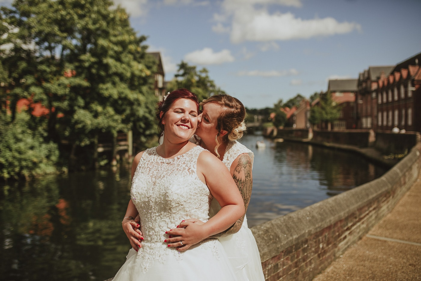 Brides kissing next to the river for wedding by Joshua Wyborn photography