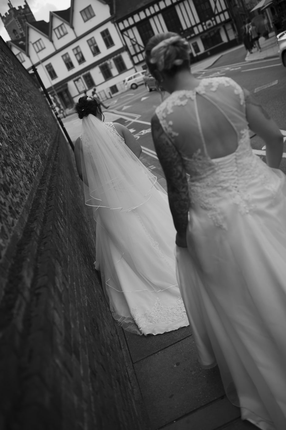 Brides walking down street together for wedding by Joshua Wyborn photography