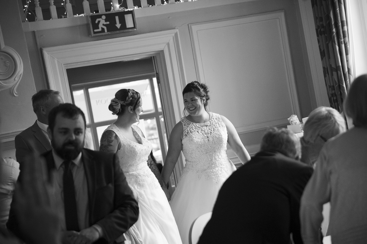 Laughing brides surrounded by guests for wedding by Joshua Wyborn photography