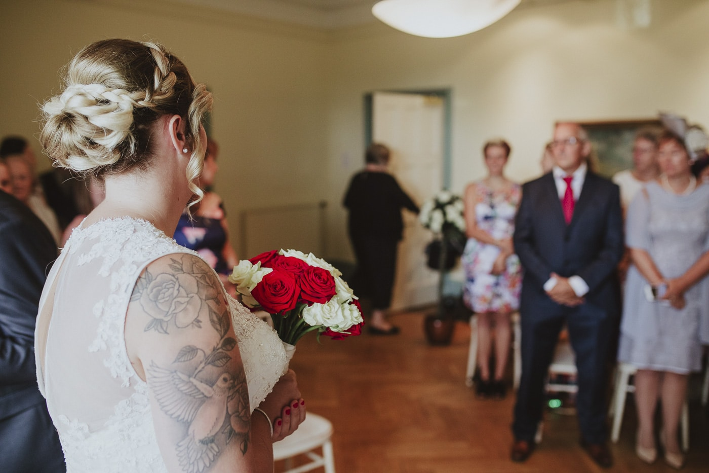 Bride waits at the end of the aisle for wedding photography by Joshua Wyborn
