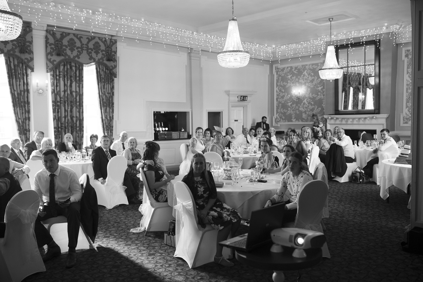 Fairy lights around the room as the guests listen to speeches for wedding by Joshua Wyborn photography