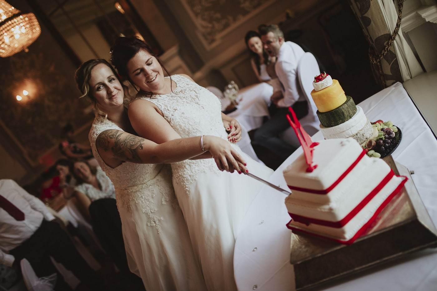 Two brides cutting the cake for wedding photography by Joshua Wyborn