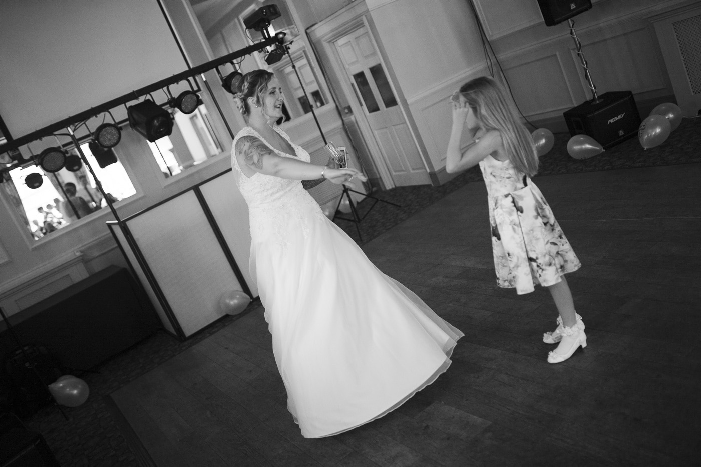 bride and girl dancing for wedding photography by Joshua Wyborn