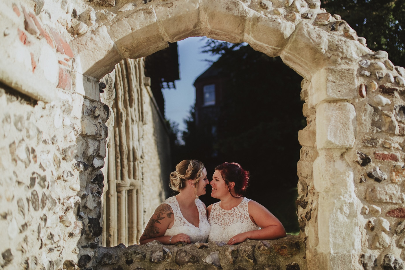 Bride and Bride through an archway for wedding photography by Joshua Wyborn