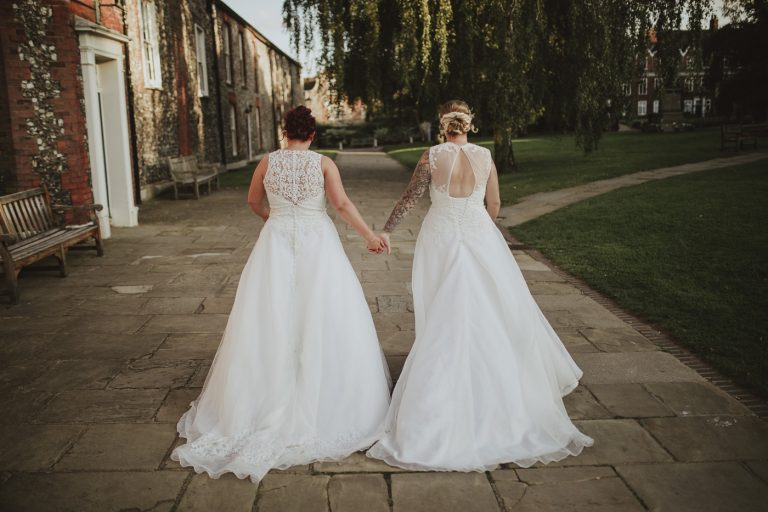 Bride and Bride holding hands as they have jsut had a same sex wedding day walking through the city centre for wedding photography by Joshua Wyborn