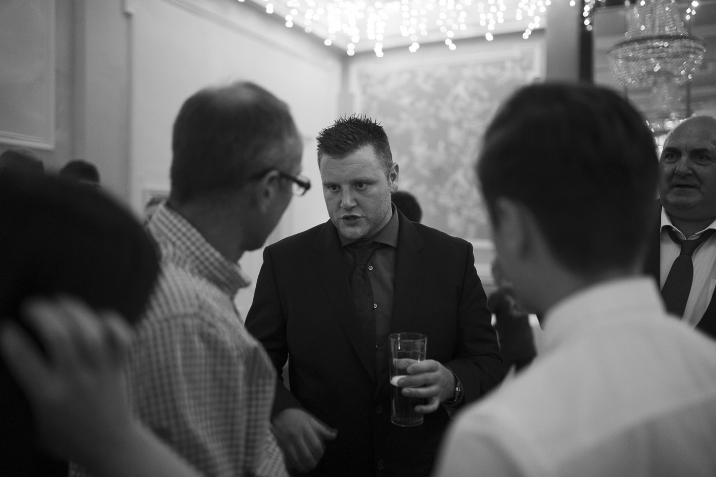 Guests chatting with drinks for wedding photography by Joshua Wyborn