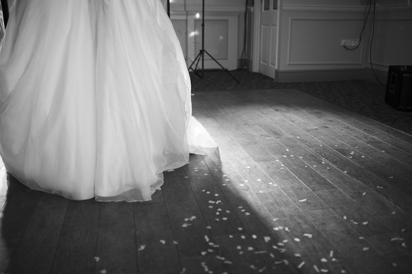 Bottom of wedding dress with confetti on the floor for wedding photography by Joshua Wyborn