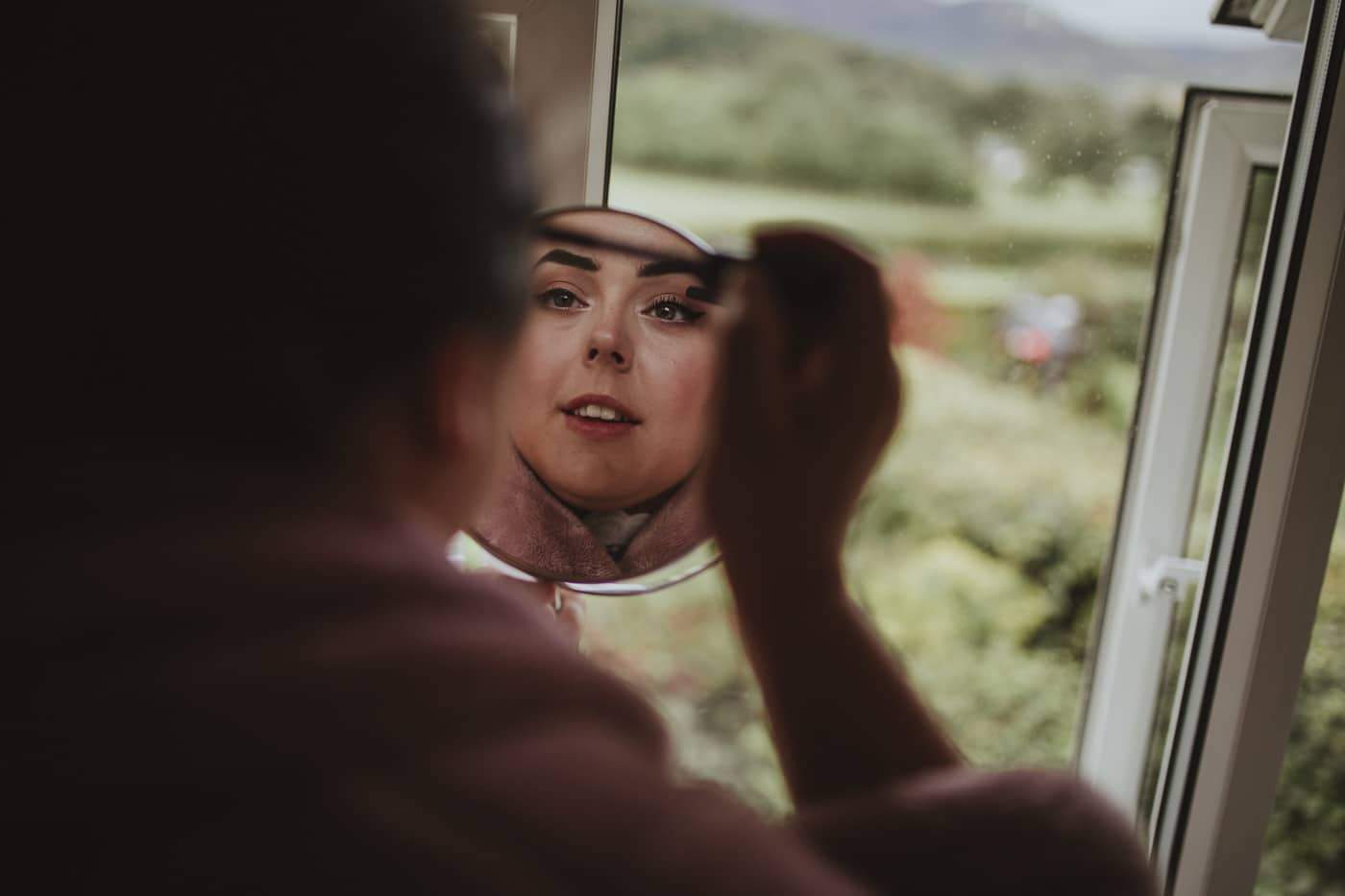 Bride doing her mascara for Cumbria wedding by Joshua Wyborn