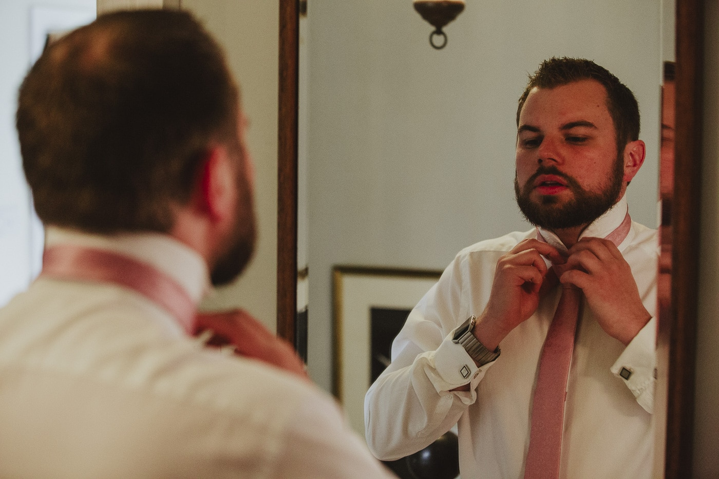 Groom doing up tie for Cumbria wedding