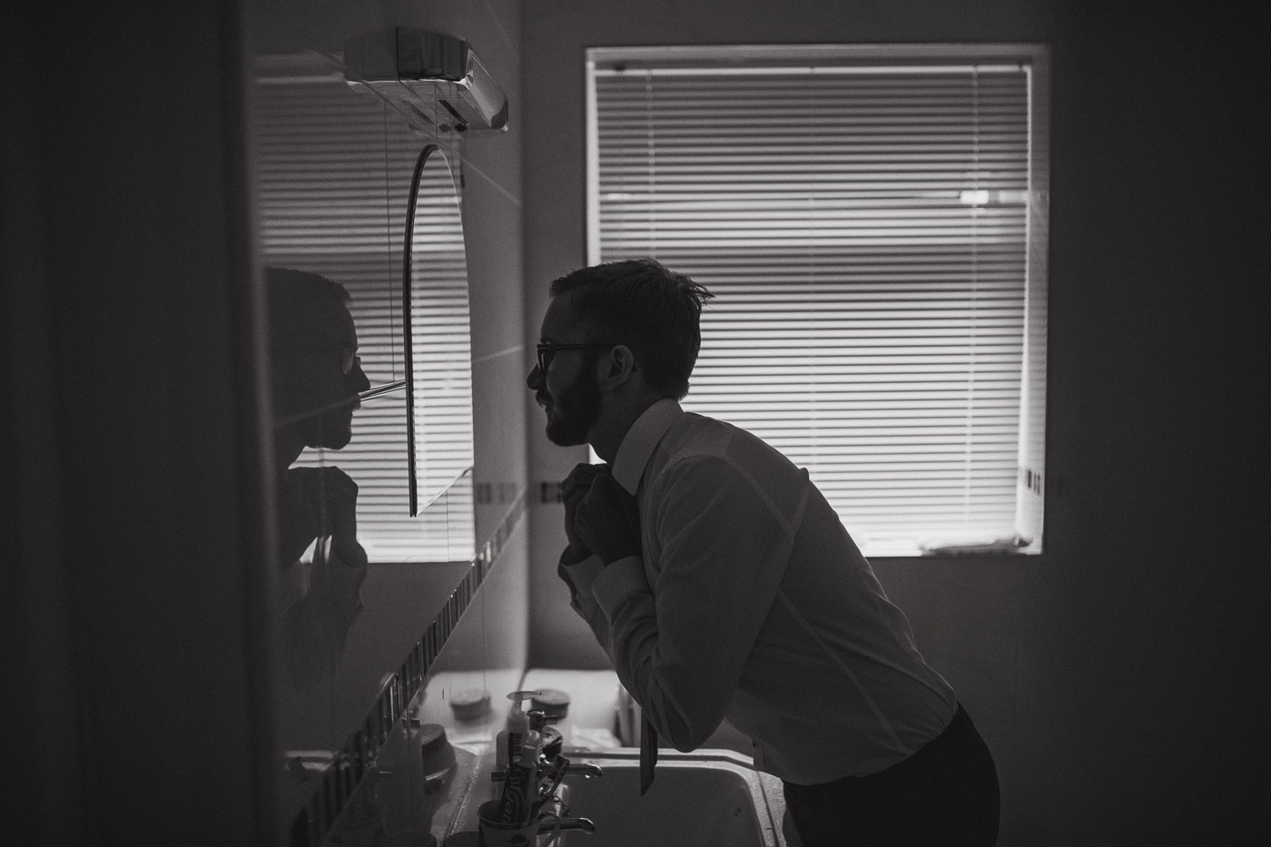 Tying tie in the mirror by wedding photographer
