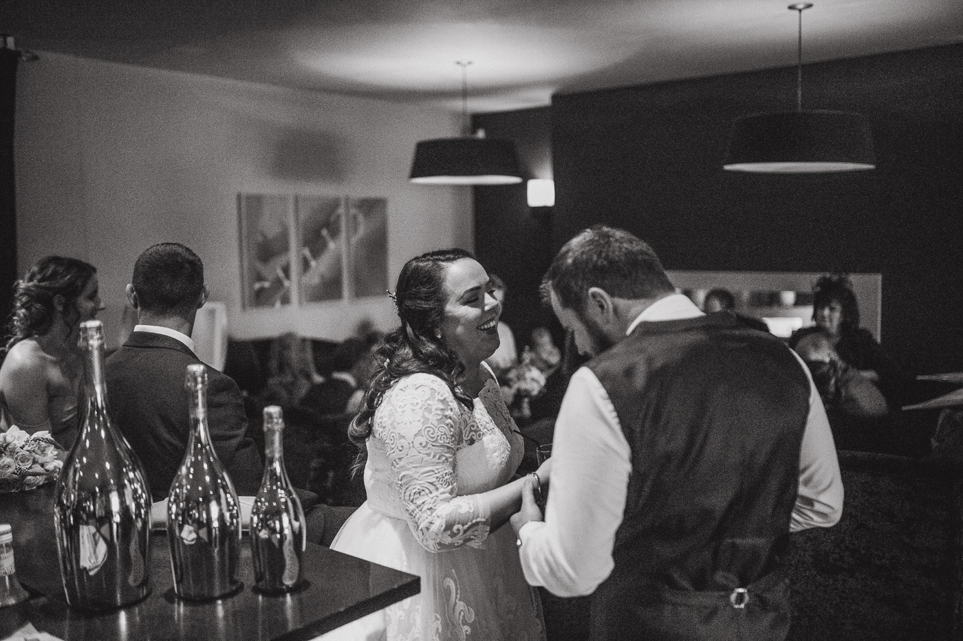 Bride and groom laughing surrounded by guests during wedding photography