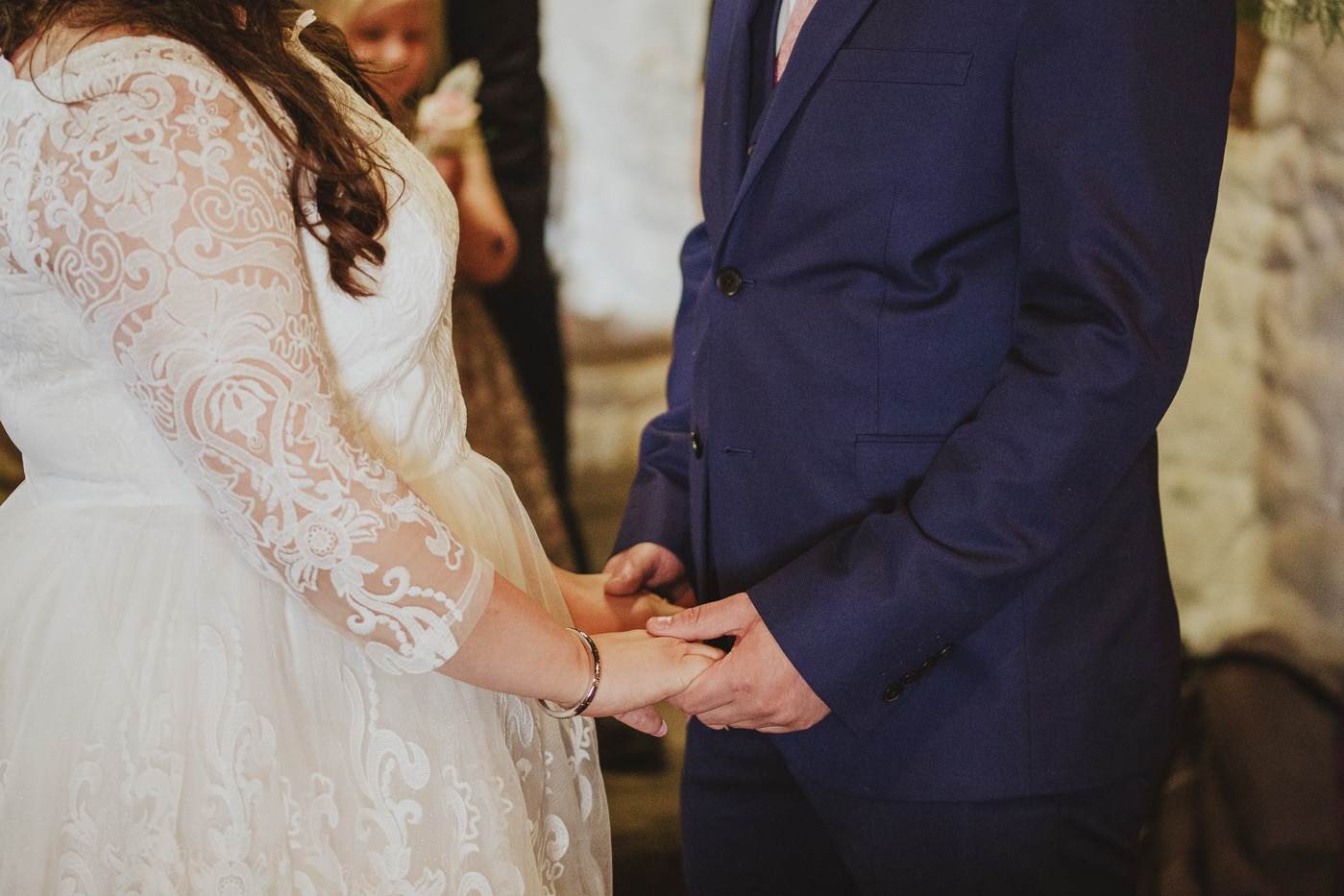 Bride and groom holding hands by Joshua Wyborn