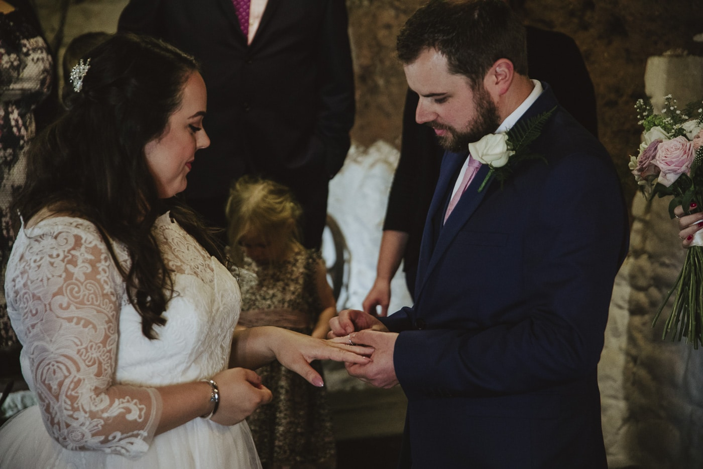 Groom giving bride her wedding ring by Joshua Wyborn