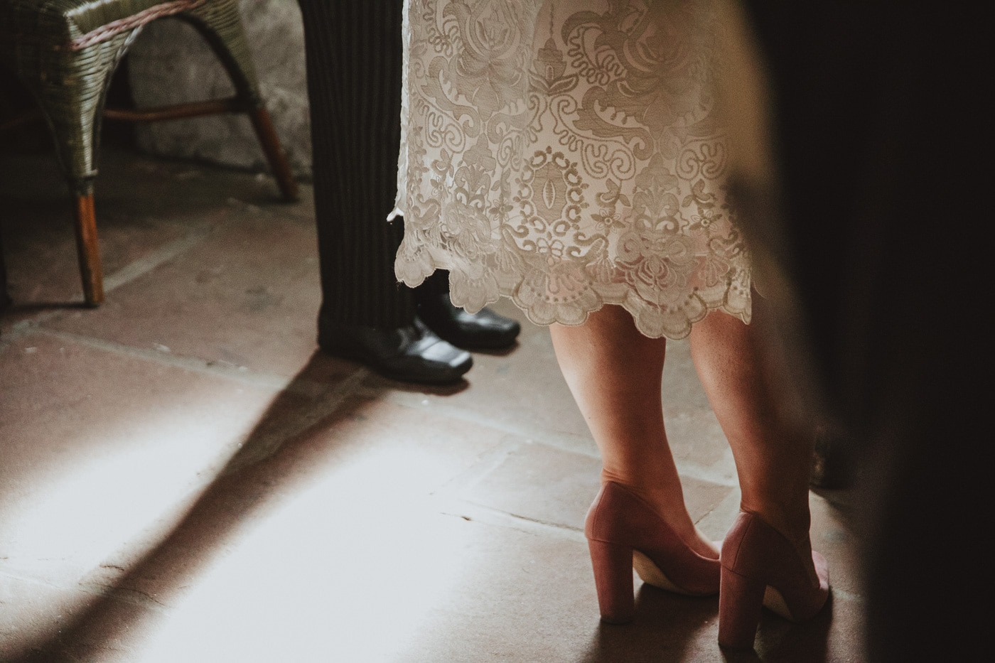 Bride and groom standing on the stone floor by Joshua Wyborn