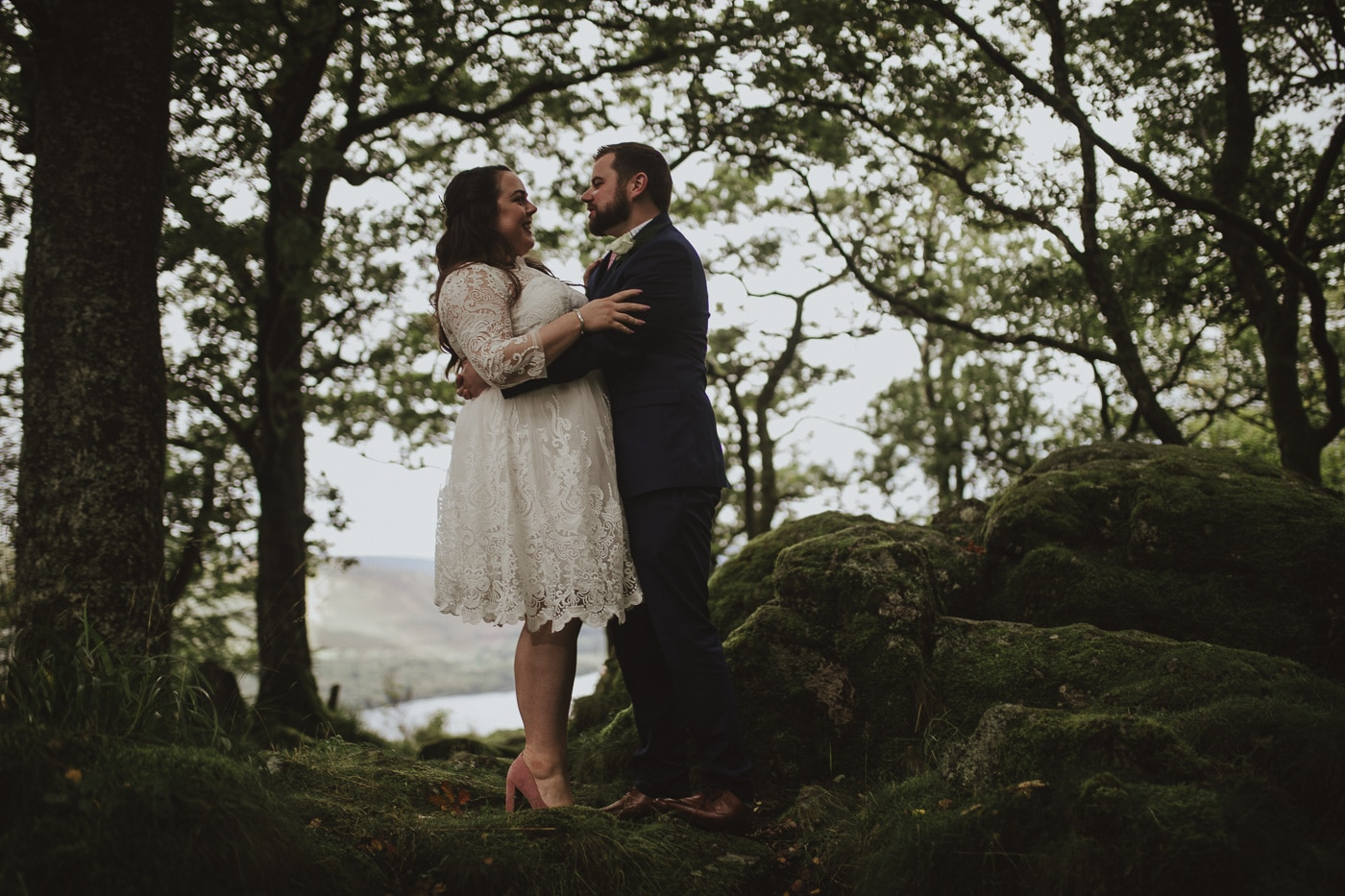 Bride and groom embracing in the forest in the lake district