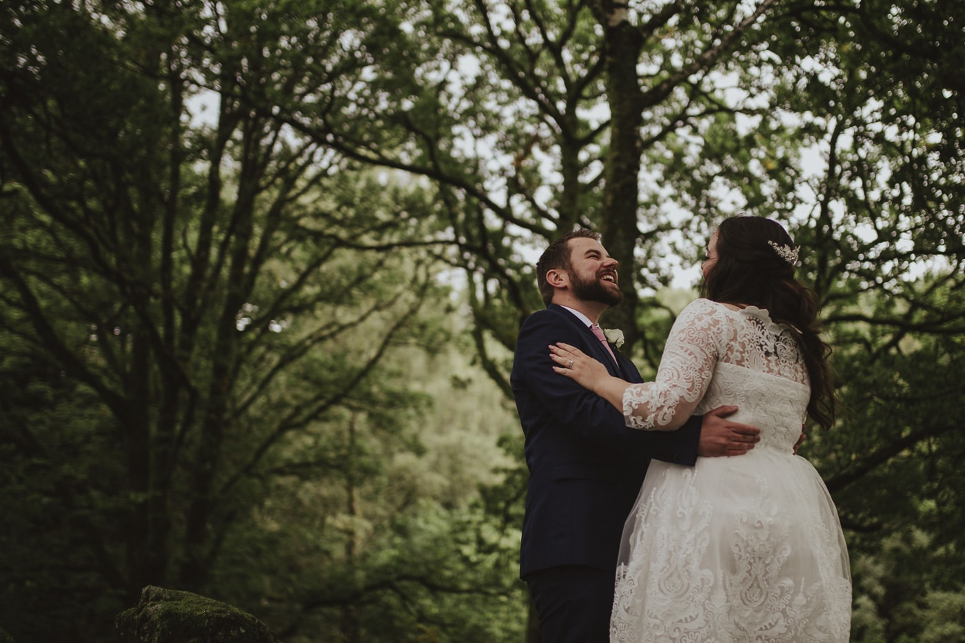 Bride and groom laughing surrounded by trees in cumbria