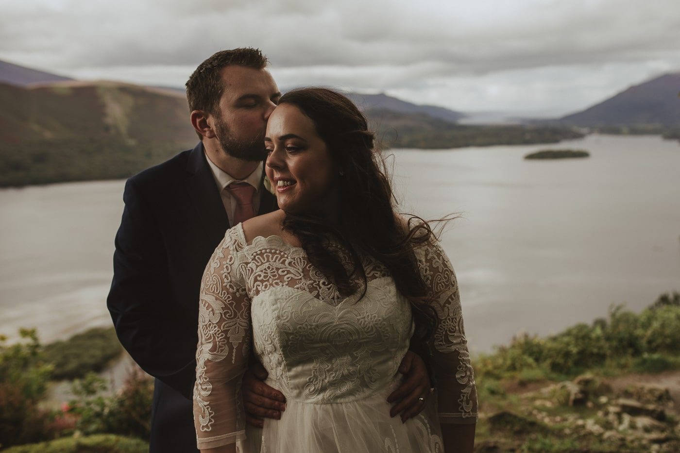 Groom kissing brides head with lake district in background