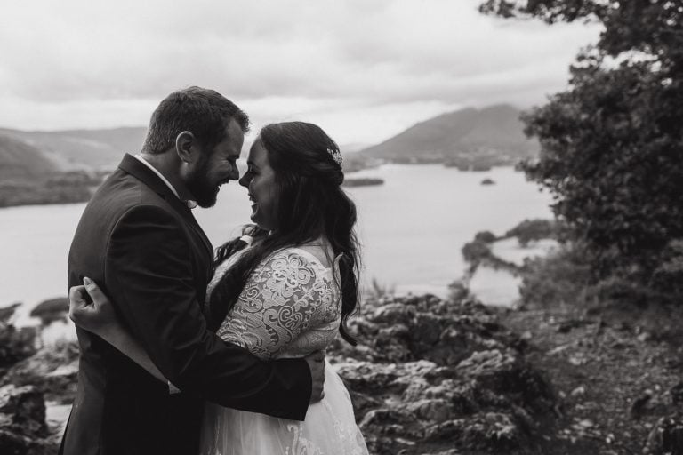 Bride and groom embracing in front of the lakes in cumbria