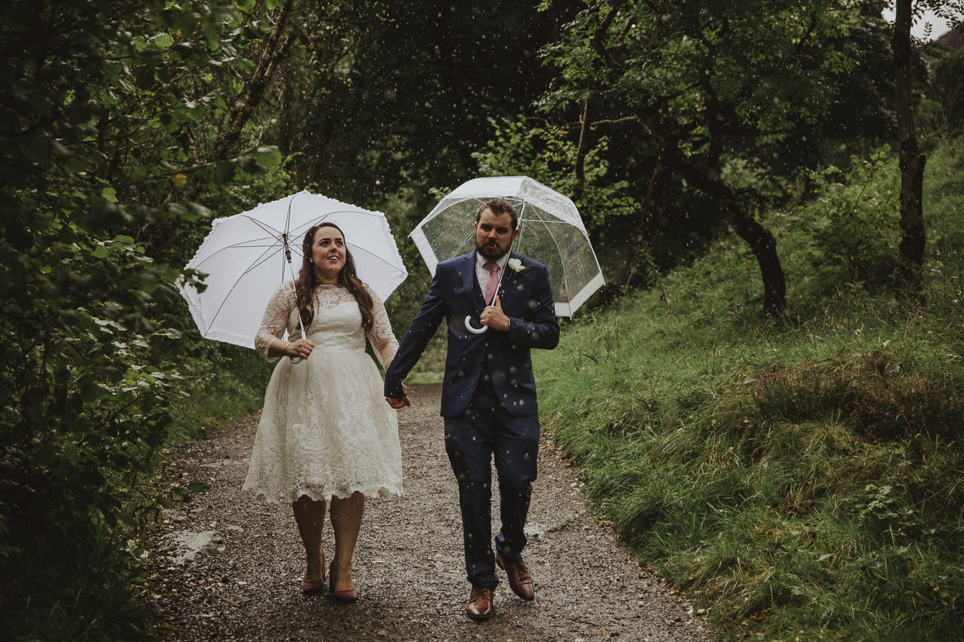 Bride and groom with umbrellas on a Lake District Elopement in Cumbria in the rain by Joshua Wyborn